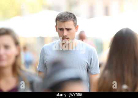 Front view portrait of a sad boy walking on the street - Stock Photo