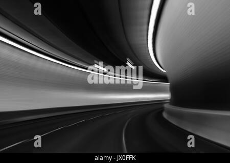 View of the brightly lit tunnel from a fast moving car; light blur exaggerates the movement; black and white - Stock Photo