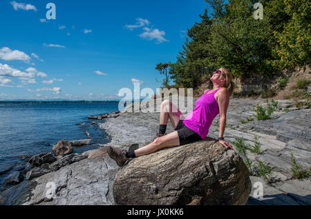 on a rocky shore of lake Champlain walking and looking out onto the lake - Stock Photo