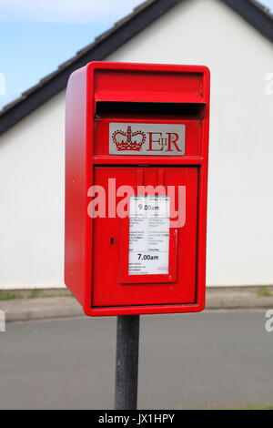 A fairly new post box besides the main road in a village with its usual red coat of paint and mounted on a post - Stock Photo