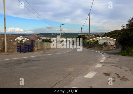 Looking along the main road in Ogmore by sea with houses on both sides and cars parked on the main road of this - Stock Photo