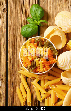 Various types of dried pasta on wooden background - Stock Photo