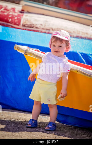 Little cute girl leaning on a colourful wooden boat in harbour in La Gomera island, Canary Islands, Spain - Stock Photo