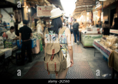 woman tourist walking in Amphawa street on Thailand travel shopping during Asia summer vacation. Traditional floating - Stock Photo