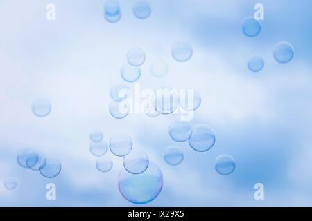 Rainbow Soap Bubbles on Blue Sky Background - Stock Photo