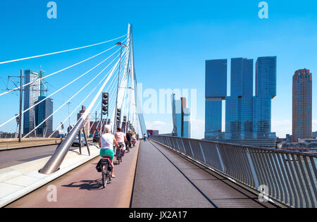 Rotterdam, The Nederlands - July 18, 2016:  Cyclists crossing the Erasmus bridge on the Maas river with the De Rotterdam - Stock Photo