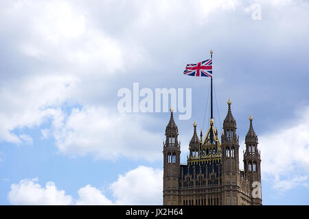 Union Jack waving on top of Victoria tower, Houses of Parliament,Westminster London.Blue sky with clouds on background,fair - Stock Photo