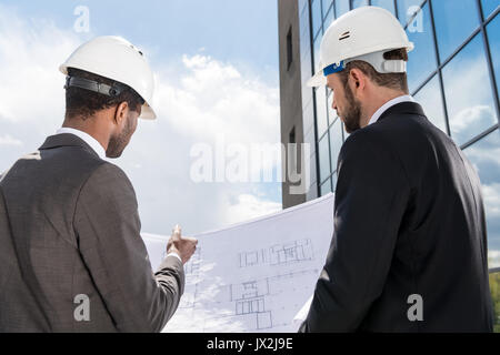 Back view of professional architects in hardhats working with blueprint - Stock Photo