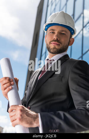 Professional architect in hard hat holding blueprint and looking at camera - Stock Photo