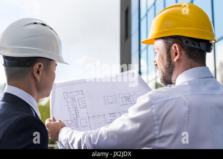 back view of professional architects in hard hats discussing project  - Stock Photo