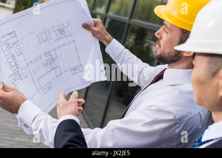 side view of professional architects in hard hats discussing project, successful businessmen concept  - Stock Photo