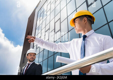 low angle view of professional architects in hard hats discussing project, successful businessmen concept  - Stock Photo