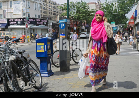A Muslim woman in a hijab & traditional dress walks on 74th St. in Jackson Heights, Queens while chatting on her - Stock Photo