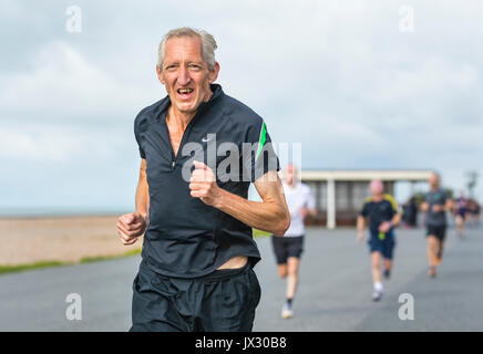 Elderly man running on the weekly Vitality Parkrun event in Worthing, West Sussex, England, UK. - Stock Photo