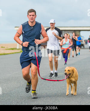 Runner with a dog on the weekly Vitality Parkrun event in Worthing, West Sussex, England, UK. - Stock Photo