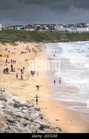 UK Weather.  Holidaymakers enjoying themselves on Fistral Beach despite dark clouds gathering.