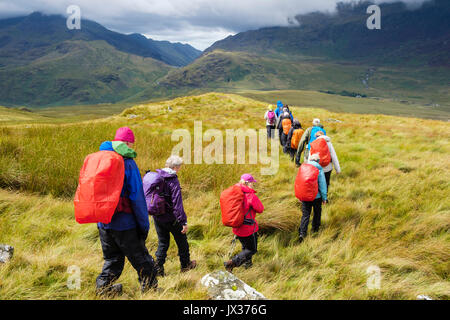 People wearing raingear on Carnedd y Cribau hiking down to Pen Y Gwryd in sunshine following wet weather rain in - Stock Photo