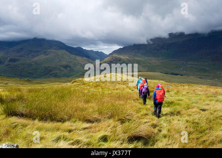 Ramblers group on Carnedd y Cribau hiking down to Pen Y Gwryd in sunshine following rain in mountains of Snowdonia - Stock Photo