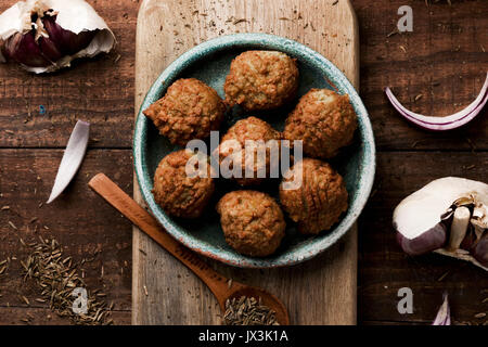 high-angle shot of some falafel served in a green earthenware plate placed on a rustic wooden table - Stock Photo