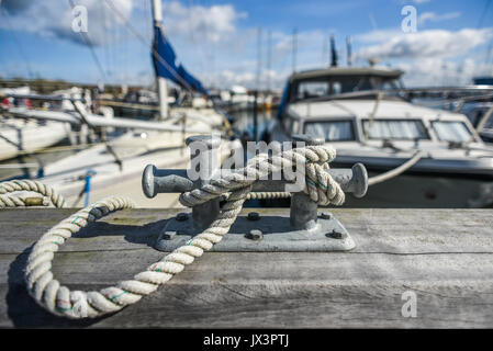 Old  harbor mooring in the background of the summer marina on a sunny day. - Stock Photo