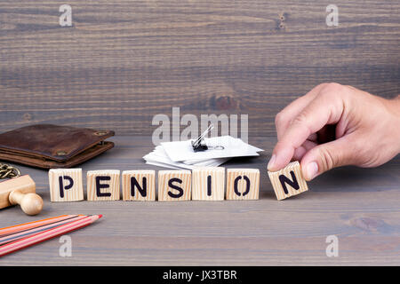 pension concept.Wooden letters on dark background. Office desk - Stock Photo