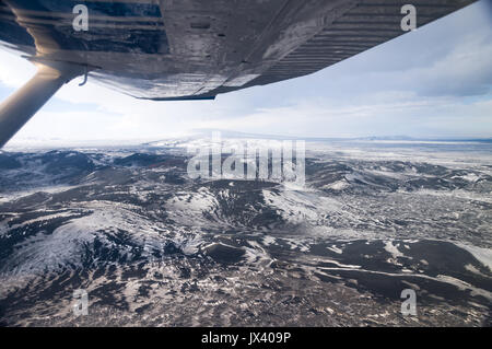 Aerial view from plane interior of Iceland snow and ice capped mountains - Stock Photo