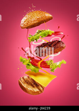 The hamburger with flying ingredients on rose background - Stock Photo