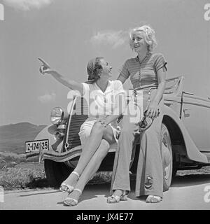 Two women sitting on front of car. - Stock Photo