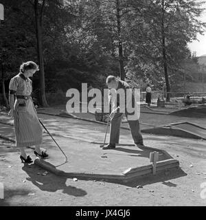 Man and woman playing miniature golf. - Stock Photo