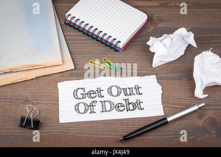 Get Out of Debt. paper sheet from the booklet on the wooden table. - Stock Photo