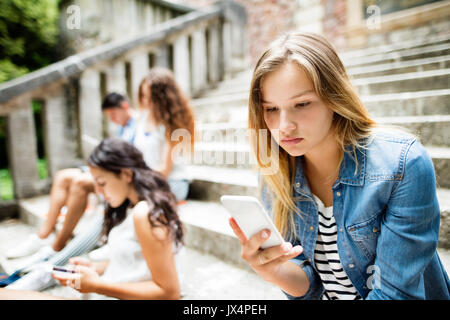 Attractive teenage student girl sitting on stone steps with her friends in front of university holding smart phone, - Stock Photo