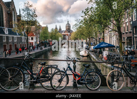 Amsterdam, Netherlands - 25 April, 2017: Bicycles parked along the bridge. Red-light district De Wallen, View of - Stock Photo