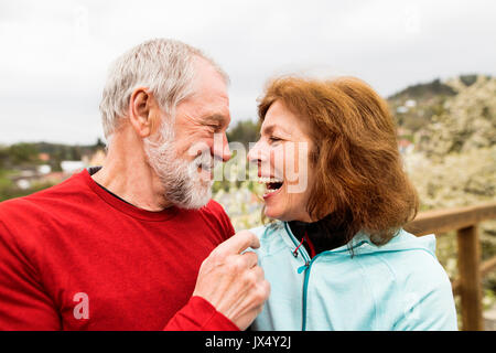 Beautiful active senior runners resting outside in sunny spring town, laughing. - Stock Photo