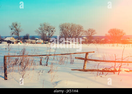 Snowy rural landscape with wooden fence, field with blue sky, trees, and village in winter - Stock Photo