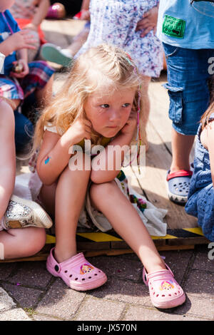 Caucasian blonde girl, child, 6-7 years old, sitting down on deck among other children. Long blonde hair, hunched - Stock Photo