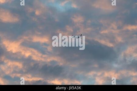 Silvertown, London, UK. 14th August 2017. UK Weather: Flight departure from London city flight into cloudy orange - Stock Photo