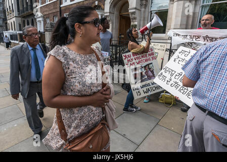 London, UK. 14th Aug, 2017. London, UK. 14th August 2017. People attending the Vedanta AGM walk past the noisy protest - Stock Photo