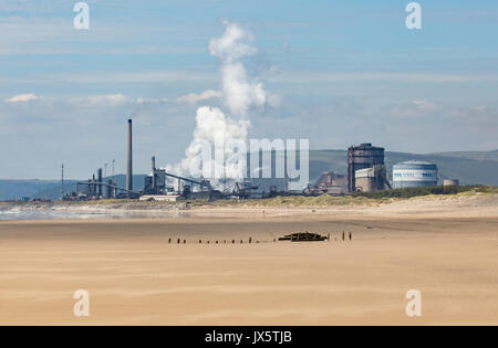 Port Talbot steel works owned by Tata Steel Co of India seen from Kenfig Burrows beach with sunken shipwreck in - Stock Photo