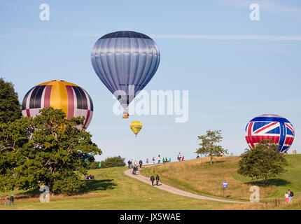 Hot air balloons landing at Ashton Court Somerset after mass ascent from the launch site during the 2017 Bristol Balloon Fiesta