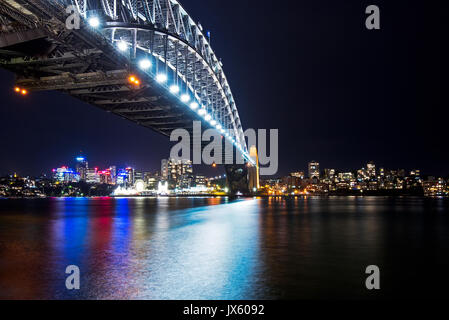 Colorful light reflection at Sydney Harbour Bridge at Night from Circular Quay, Sydney, Australia - Stock Photo