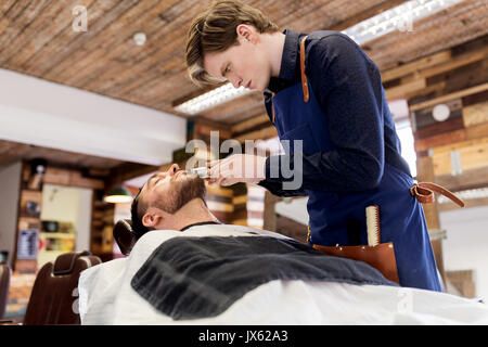 man and barber with trimmer cutting beard at salon - Stock Photo