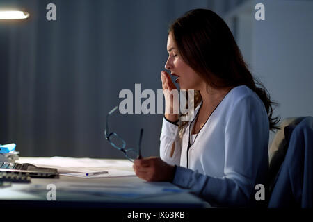 tired woman with glasses yawning at night office - Stock Photo