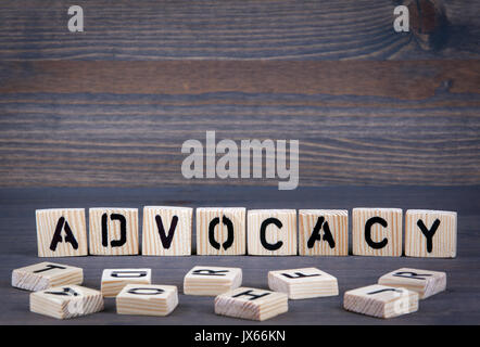 Advocacy word written on wood block. Dark wood background with texture. - Stock Photo