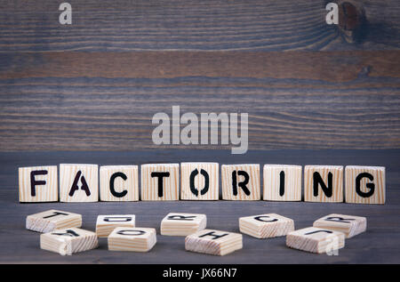 Factoring word written on wood block. Dark wood background with texture. - Stock Photo