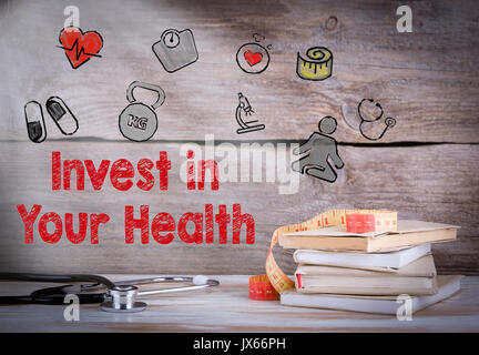 Invest in your health. Stack of books and a stethoscope on a wooden background. - Stock Photo