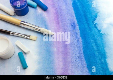 striped abstract blue watercolor background with paper texture and paintbrushes on it - Stock Photo