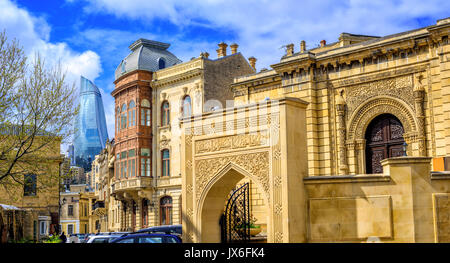 Panoramic view of Baku Old Town (Icheri Sheher), Azerbaijan, with modern glass Flame Tower skyscraper in background - Stock Photo
