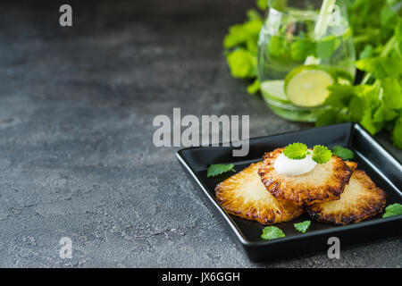 Fried pineapple slices with creme fraiche, mint on dark background. Copy space - Stock Photo