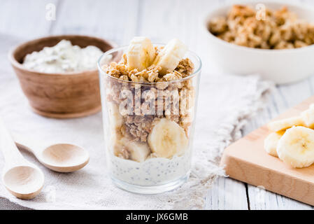 Chia pudding parfait, layered yogurt with banana, granola. Healthy breakfast concept on white wooden table - Stock Photo