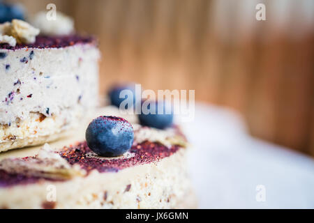 Raw blueberry cheesecake, homemade with decoration of dried flowers and fresh berries. Healthy handmade dessert. - Stock Photo